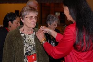 Tamara Fode pins the Vietnam Commemorative pin on Carol Mutter.